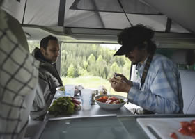 Männer essen im gemieteten Kastenwagen